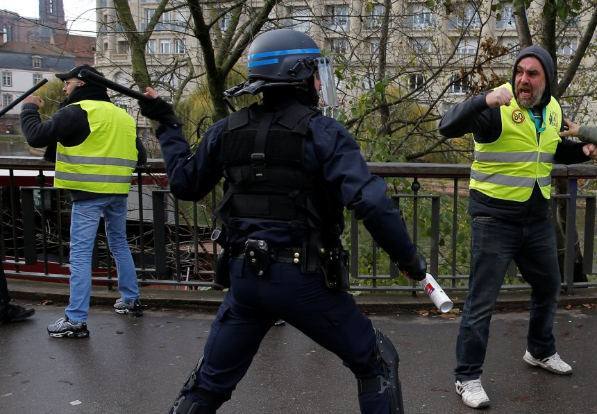 Protesters wearing yellow vests, a symbol of a drivers' protest against higher diesel fuel prices, face off with French riot police as they demonstrate in Strasbourg